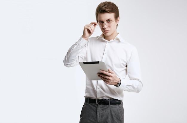 Уверен молодой бизнесмен в рубашке, работающих на цифровой планшет
