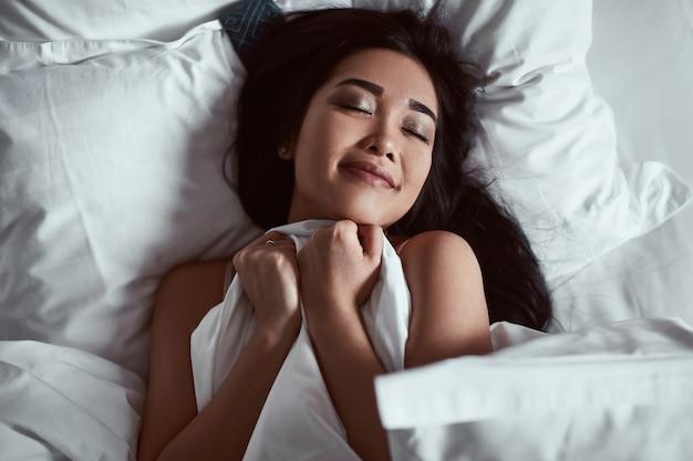 Портрет красивой чувственной азиатской женщины под одеялом