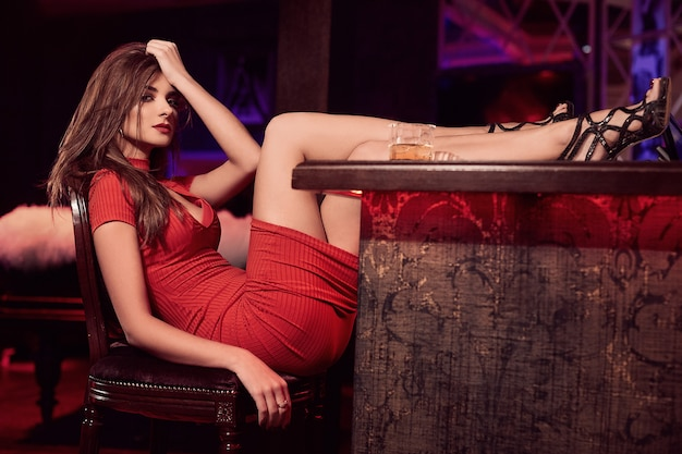 ウイスキーのグラスと赤いドレスのゴージャスな美しさ若いブルネットの女性