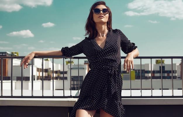 建物の屋根でポーズをとってファッションドレスでゴージャスな明るいブルネットの女性