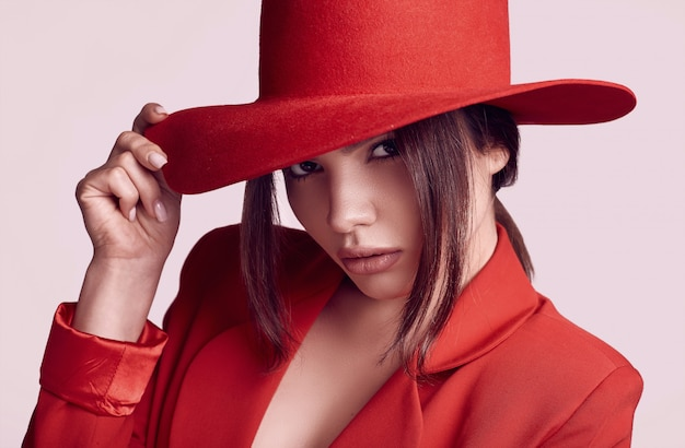 赤いファッショナブルなスーツと広い帽子でエレガントな美しい女性