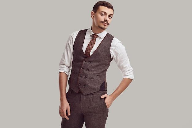 ウールの茶色のスーツに口ひげを持つハンサムな若いアラビア語ビジネスマン