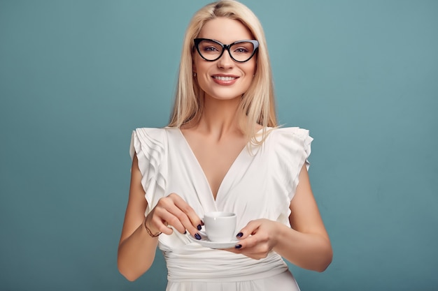 Великолепная чувственная блондинка в белом платье с чашкой кофе