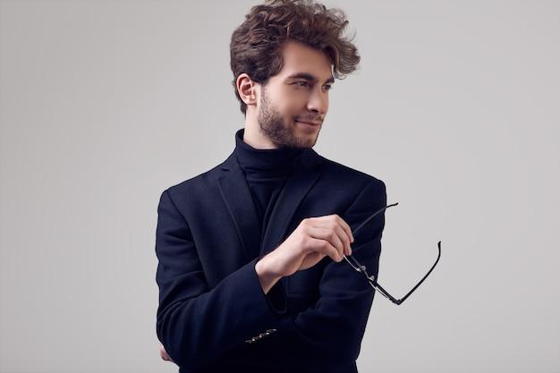 Красивый элегантный мужчина с вьющимися волосами в костюме и очках
