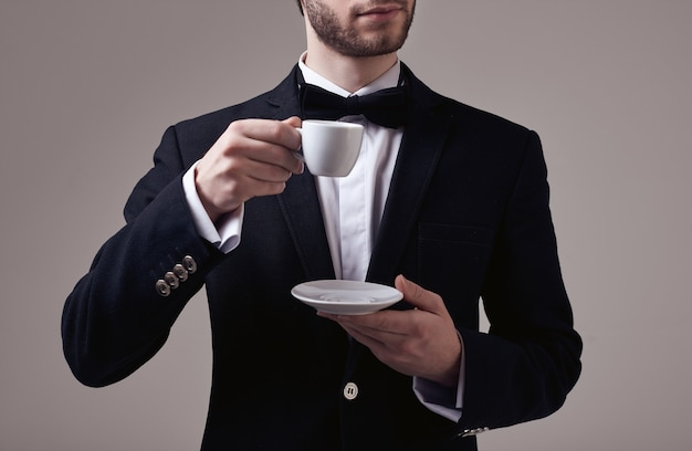エスプレッソのカップを保持しているタキシードで巻き毛のハンサムなエレガントな男
