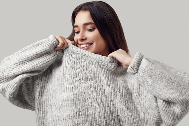 Красивая брюнетка женщина в свитер позирует в студии