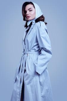 Молодая элегантная брюнетка в пальто и платке позирует в студии