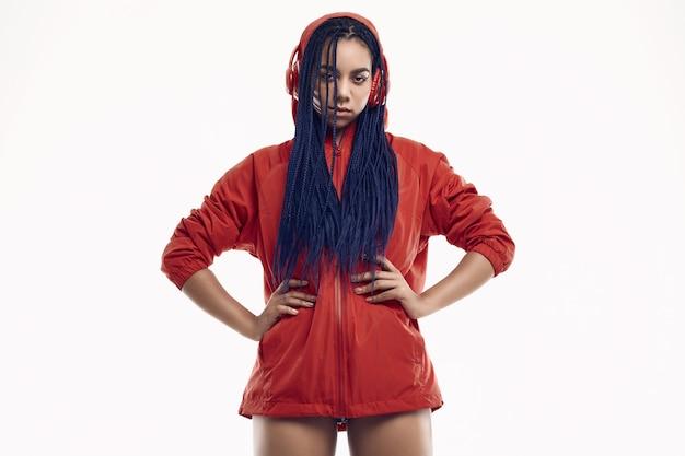 Африканская девушка с дредами в красной ветровке слушает музыку