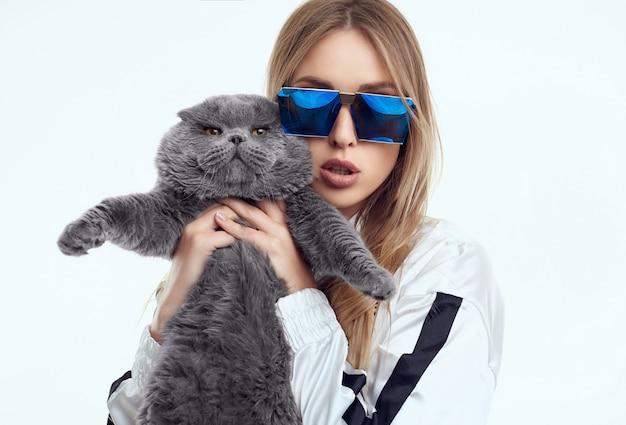 太った血統の猫とポーズのトラックスーツでゴージャスなモデルの女の子