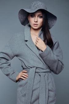 Молодая модная брюнетка женщина красота в сером пальто и шляпу