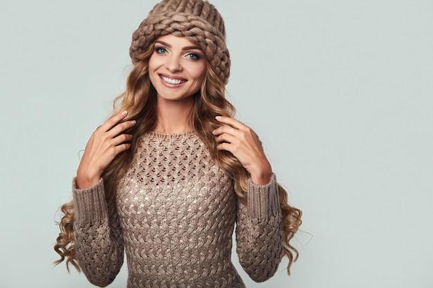 Портрет красивой улыбающейся белокурой женщины в свитере