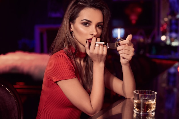 タバコとウイスキーの赤いドレスの豪華な美しさ若いブルネットの女性