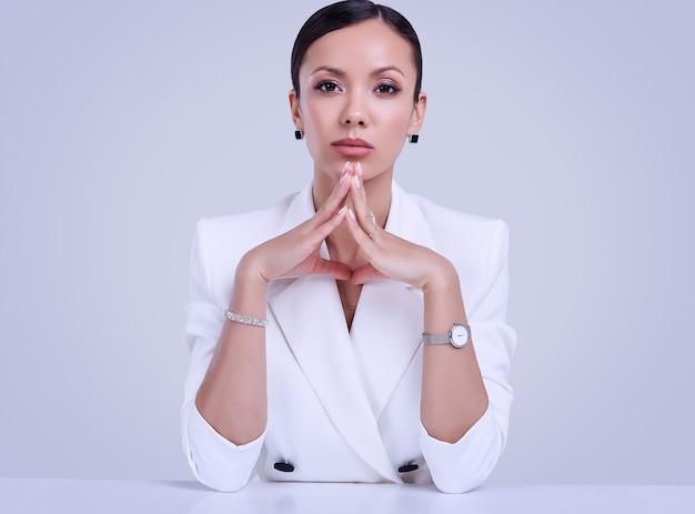 Великолепные латинские женщины в модном белом костюме носят дорогие украшения