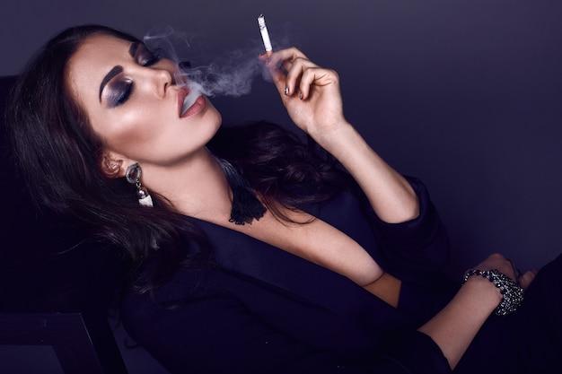 タバコを吸ってエレガントなホットブルネットの女性