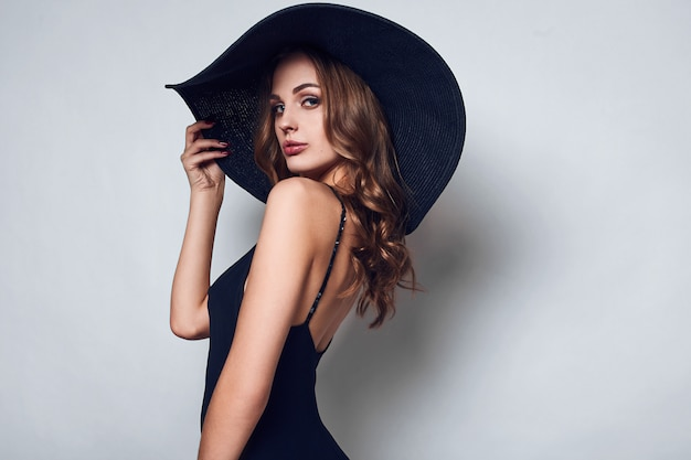黒のドレスと帽子でエレガントな美しい女性