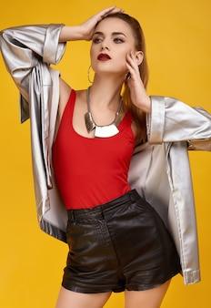 Элегантная гламурная хипстерская девушка в красном топе, черных шортах и джинсовой куртке