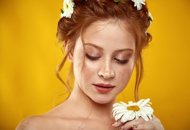 彼女の頭にカモミールクラウンと美しい肯定的な赤毛の女の子