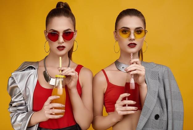 Две элегантные гламурные хипстерские девушки-близнецы в модном красном топе с коктейльным напитком