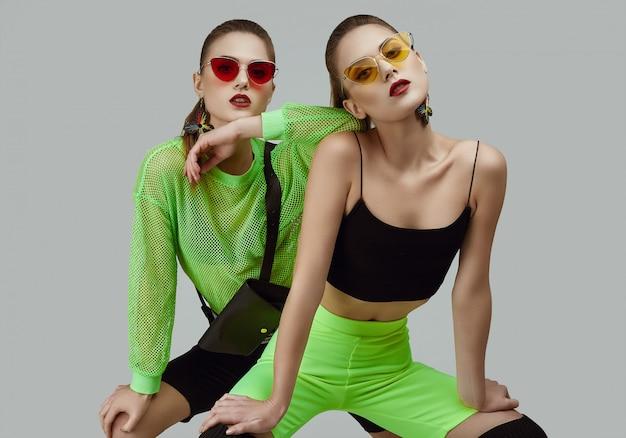 Две элегантные гламурные хипстерские двойняшки в моде неоновые зеленые платья
