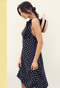 白い壁にポーズの帽子とファッションのドレスでゴージャスなブルネット