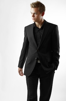 スタジオの背景に黒のスーツでセクシーな男性モデル