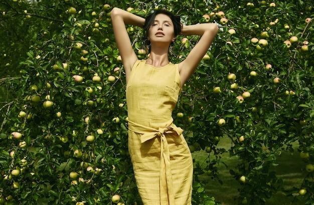 Великолепная брюнетка в моде желтое платье в яблоневом саду
