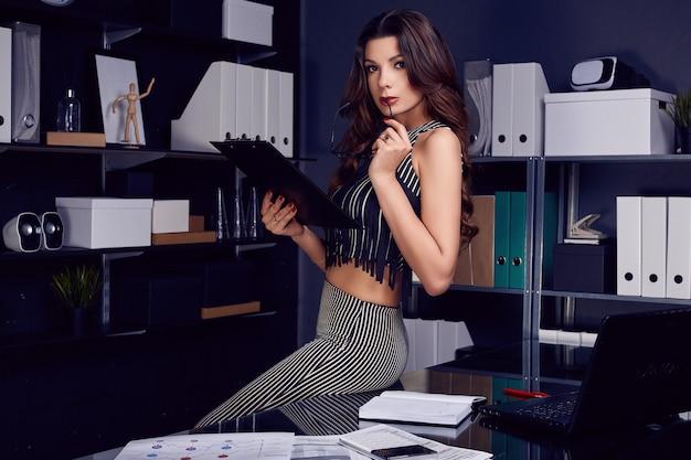 Молодая красивая деловая женщина работает на стильный черный стол