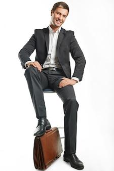 Красивый молодой деловой человек в черном костюме держит чемодан