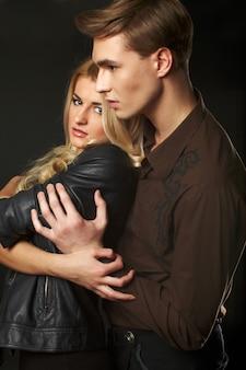 スタジオでセクシーな若いヒップなカップルの肖像画