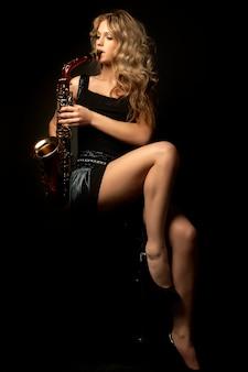 サックスとセクシーな魅力的な金髪の女性モデル