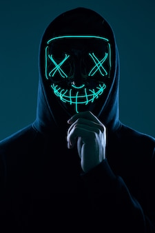 Анонимный мужчина в черной толстовке с капюшоном прячет лицо за неоновой маской