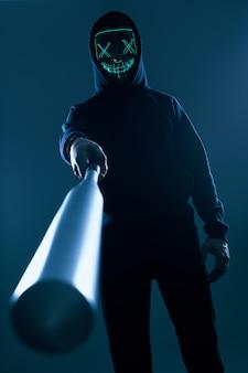 Анонимный преступник с бейсбольной битой в черной толстовке и неоновой маске