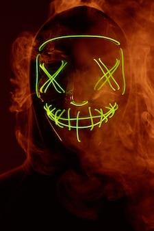 色付きの煙でネオンマスクの後ろに顔を隠す匿名の男