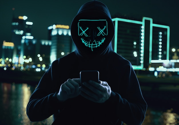 Анонимный мужчина в черной балахоне и неоновой маске взламывает смартфон