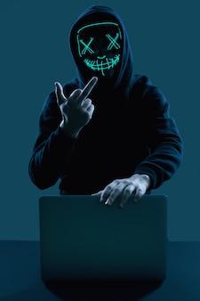 コンピューターにハッキングする黒いパーカーとネオンマスクの匿名の男