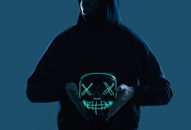 ネオンマスクの後ろに顔を隠して黒いパーカーの匿名男