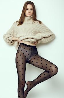 Веселая модная хипстерская девушка в уютном свитере и черных колготках