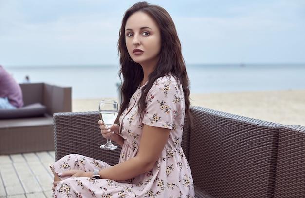 ビーチに座って夏のドレスで美しい明るい少女