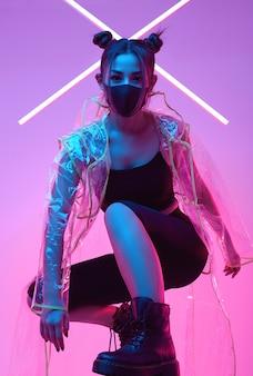Вирусная маска азиатская женщина, носящая защиту лица вокруг красочного неона