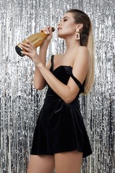 Элегантная чувственная блондинка в черном платье с бутылкой шампанского