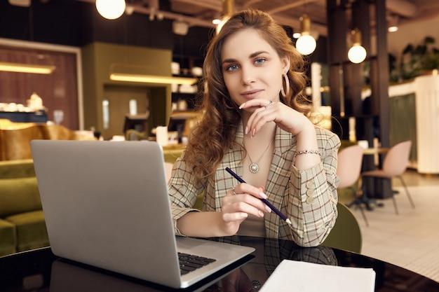 Молодая коммерсантка в умной вскользь одежде делает примечания в тетради в интерьере кофейни