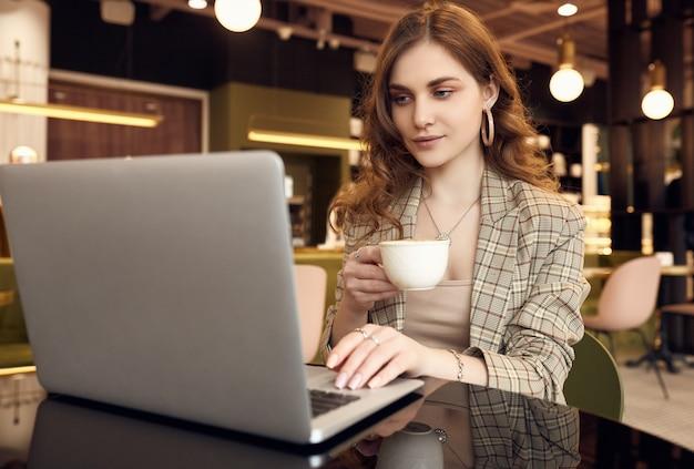 Молодая деловая женщина в элегантной повседневной одежде пьет кофе и работает на ноутбуке