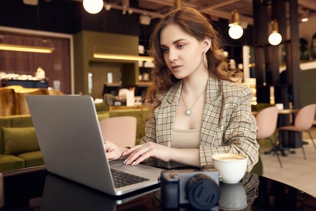 Уверенно фотограф молодой женщины в умной вскользь одежде работая на компьтер-книжке