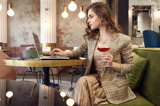 Молодая деловая женщина в элегантной повседневной одежде пьет вино и работает на ноутбуке