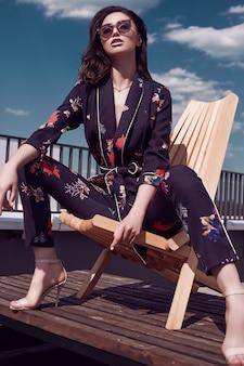 Шикарная брюнетка в яркой одежде сидит на деревянном стуле