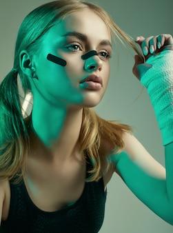 ブロンドの髪、自信に満ちた表情、保護ボクシング包帯の拳で強い美しい少女
