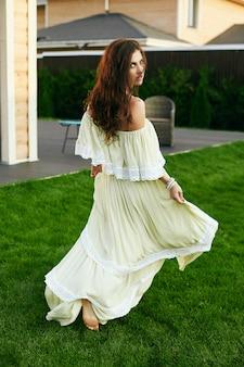 Чувственная брюнетка в модном платье позирует в саду