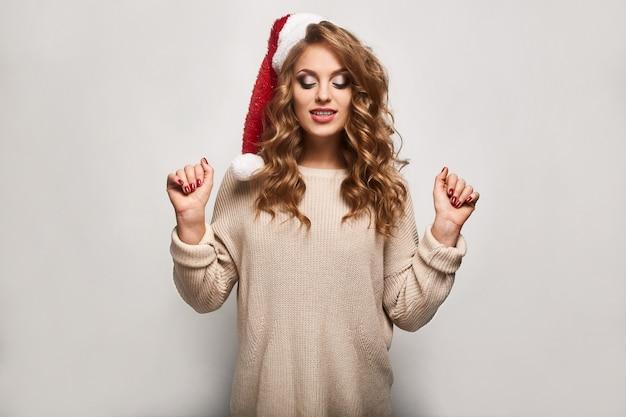 セーターとお祝いキャップの美しい肯定的なブロンド