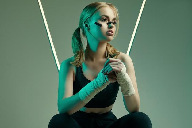 Сильная красивая женщина со светлыми волосами, уверенным взглядом, кулаками в защитных боксерских повязках