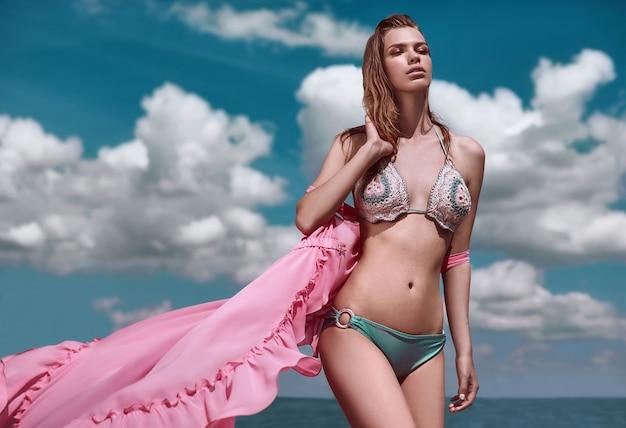 Модная, соблазнительная девушка в вязаном купальнике и парео